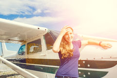 Young happy woman standing near private plane royalty free stock photography