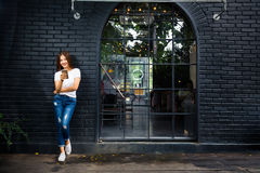 Young happy woman standing outside a coffee shop using her phone Royalty Free Stock Photos