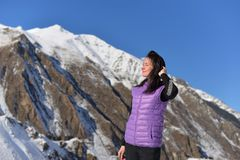 Young happy woman standing smiling in snowy mountains stock photo