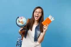 Young happy woman student in glasses with backpack holding world glove, passport, boarding pass tickets isolated on blue. Background. Education in university royalty free stock photography