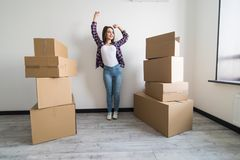 Young happy woman, a student, moved into a new apartment. Unpacks boxes in the new house and raised her hands up as a sign of succ. Young happy woman, a student royalty free stock photos