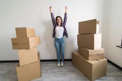 Young happy woman, a student, moved into a new apartment. Unpacks boxes in the new house and raised her hands up as a sign of succ. Young happy woman, a student stock photo