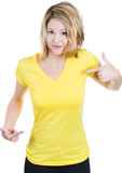 Young happy woman, student, pointing at a blank yellow t-shirt Stock Photography