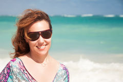 Young happy woman in sunglasses on ocean coast Royalty Free Stock Image