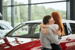 Young happy woman surprised by a new car at car showroom, gift from her husband stock photo