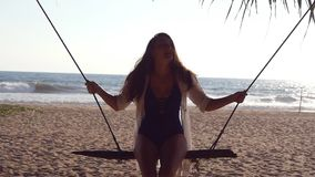 Young happy woman in swimsuit and shirt relaxing at swing at tropical ocean beach. Beautiful girl sitting on swing and. Enjoying summer vacation or holiday stock video