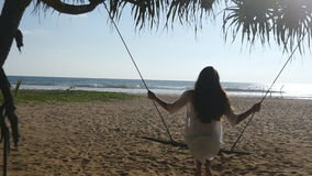 Young happy woman in swimsuit and shirt relaxing at swing at tropical ocean beach. Beautiful girl sitting on swing and. Enjoying summer vacation or holiday stock video footage