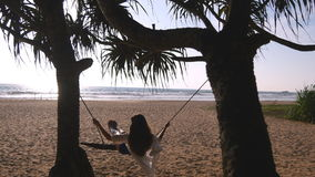 Young happy woman in swimsuit and shirt relaxing at swing at tropical ocean beach. Beautiful girl sitting on swing and Stock Photos