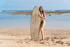 Young happy woman in swimsuit and surfboard resting on beach at sunny summer day. Surfer girl waiting for high waves on ocean. Concept of active lifestyle royalty free stock photo