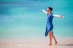Young beautiful woman on tropical seashore. Happy girl relaxing at white sand tropical beach Royalty Free Stock Photography