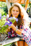 Young happy woman taking care of petunia flowers Stock Image