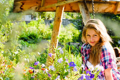 Young happy woman taking care of petunia flowers Royalty Free Stock Image