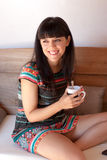 Young happy woman taking a coffee break. In a rustic sofa Royalty Free Stock Images