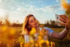 Young happy woman taking selfie in spring blooming field at sunset. Allergy free. Girl enjoys flowers Royalty Free Stock Photography