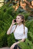 Young happy woman talking on cellphone, sitting in city park. stock photo