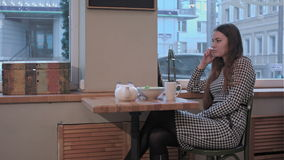 Young happy woman talking on mobile phone with friend while sitting alone in coffee shop interior stock video footage
