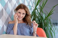 Young happy woman talking on mobile phone with friend while sitting alone in modern coffee shop interior Stock Photos