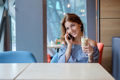 Young happy woman talking on mobile phone with friend while sitting alone in modern coffee shop interior Stock Photo