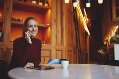 Young happy woman talking on mobile phone with her boyfriend while relaxing in cozy cafe bar after walking, Royalty Free Stock Photo