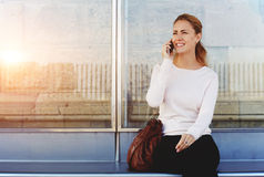 Young happy woman talking on mobile phone with her boyfriend while she waiting for a taxi or bus on a station Stock Photo