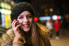 Young happy woman talking on mobile phone at night in winter Stock Image