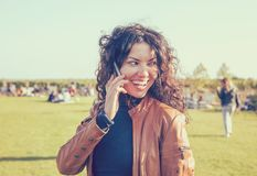 Young happy woman talking on mobile phone outdoors. Royalty Free Stock Photo