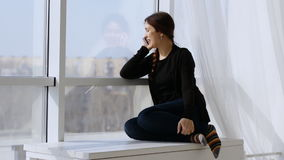 Young happy woman talking on the phone. Sitting by the window on a beautiful Sunny day stock video footage