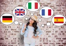 young happy woman thinking in main languages. Bricks wall background royalty free stock photo
