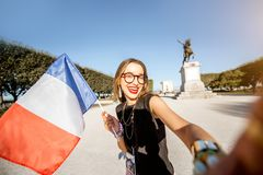 Woman traveling in Montpellier city, France. Young happy woman tourist making selfie photo with french flag at the famous Peyrou park during the morning light in royalty free stock image