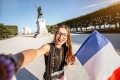Woman traveling in Montpellier city, France. Young happy woman tourist making selfie photo with french flag at the famous Peyrou park during the morning light in stock photos