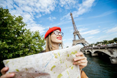 Tourist near the Eiffel tower. Young and happy woman tourist sitting with paper map in front of the Eiffel tower in Paris Stock Images