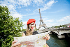 Tourist near the Eiffel tower. Young and happy woman tourist sitting with paper map in front of the Eiffel tower in Paris Royalty Free Stock Photo