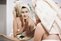 Young happy woman in towel applying organic face mask and looking at round mirror in stylish bathroom. Girl making facial massage. With scrub, peeling and royalty free stock photo