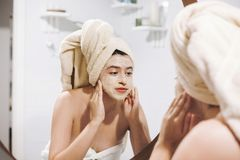 Young happy woman in towel applying organic face mask and looking at round mirror in stylish bathroom. Girl making facial massage. With scrub, peeling and stock photography
