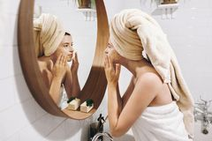 Young happy woman in towel applying organic face mask and looking at round mirror in stylish bathroom. Girl making facial massage. With scrub, peeling and stock photos