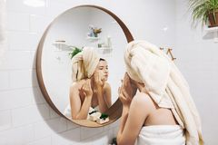 Young happy woman in towel making facial massage with organic face scrub and looking at mirror in stylish bathroom. Girl applying. Scrub cream, peeling and stock photography
