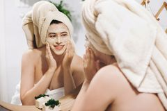 Young happy woman in towel making facial massage with organic face scrub and looking at mirror in stylish bathroom. Girl applying. Scrub cream, peeling and stock photo