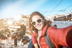 Young happy woman travel girl traveler makes selfie on a smartphone on the background of Porto, travel to Portugal, a popular royalty free stock photos