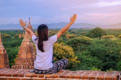 Young happy woman traveling, Asian traveler on Pagoda and looking Beautiful ancient temples, landmark and popular for tourist. Attractions in Bagan, Myanmar royalty free stock photo