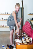 Young happy woman trying on pair of sandals Royalty Free Stock Image