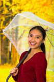Young happy woman with umbrella wearing a red sweater at beautiful autum park Royalty Free Stock Photos