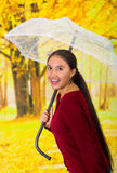 Young happy woman with umbrella wearing a red sweater at beautiful autum park Stock Image