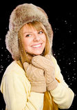 Young happy woman under snowfall. Isolated over black Stock Photography