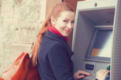 Young happy woman using ATM Royalty Free Stock Photos