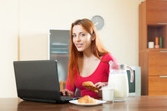Young  happy woman using laptop during breakfast at home Royalty Free Stock Photo