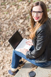 Young happy woman using laptop on stairs in park Royalty Free Stock Images