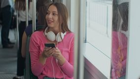 Young and happy woman using smartphone while sitting near the window in the public transport during the trip. Young and happy woman using smartphone while stock footage