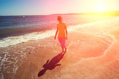 Young woman walking barefoot  on the beach Royalty Free Stock Photography