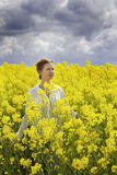 Young happy woman is walking in canola field Stock Photos