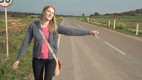 Young happy woman walking by a countryside road hitchhiking. Looking for a ride to start a journey. Young happy woman walking by a countryside road hitchhiking stock video footage